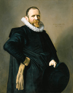 Portrait of a standing man holding a hat